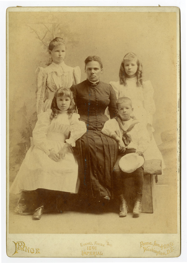 [LARGE CABINET CARD PHOTOGRAPH OF AN AFRICAN AMERICAN WOMAN AND FOUR WHITE CHILDREN]. African-American Photographica.
